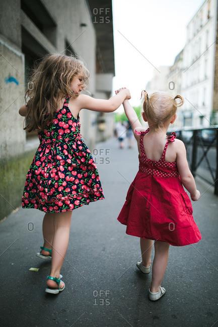 Two little girls walking down Parisian sidewalk