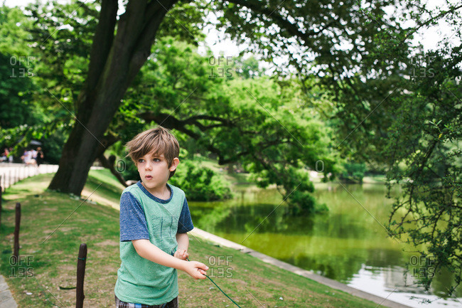 Boy standing in park in summer staring off