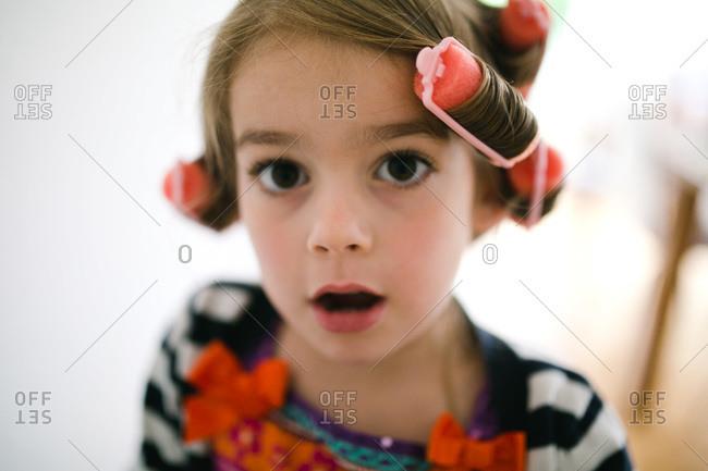 Little girl in curlers looking shocked