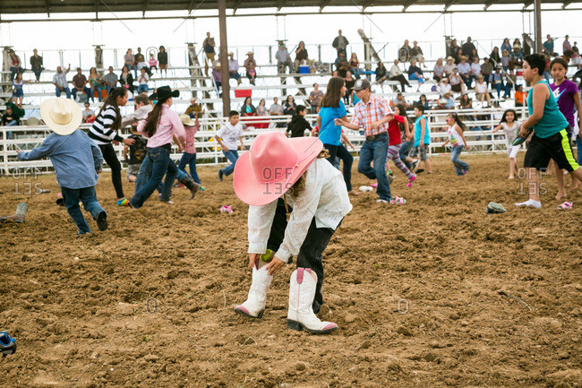 Taos, New Mexico, USA - June 28, 2015: Little girl putting on cowboy boots