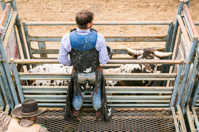 Taos, New Mexico, USA - June 28, 2015: Rodeo competitor standing at a bull chute