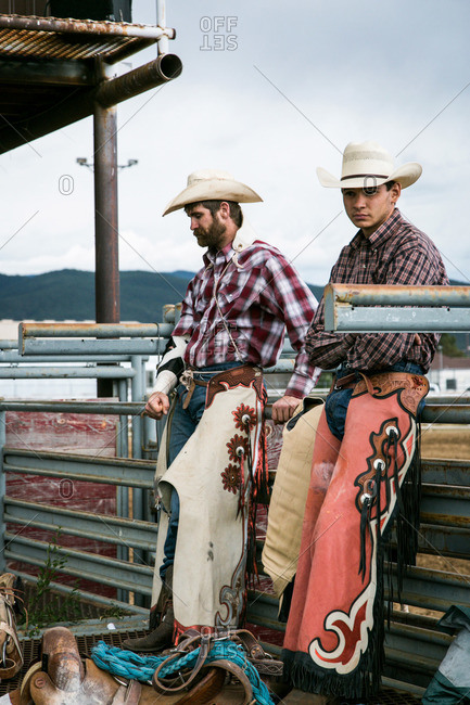 Taos, New Mexico, USA - June 28, 2015: Two cowboys leaning against a fence