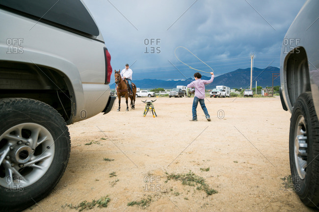 Taos, New Mexico, USA - June 28, 2015: Boy practicing roping on a stationary bull