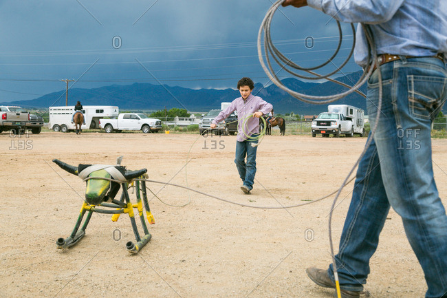 Taos, New Mexico, USA - June 28, 2015: Boy throwing a rope at a stationary bull