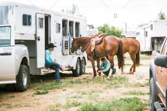 Taos, New Mexico, USA - June 28, 2015: Women and horses outside of a horse trailer