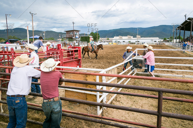 Taos, New Mexico, USA - June 28, 2015: Men leaning against a fence at a rodeo