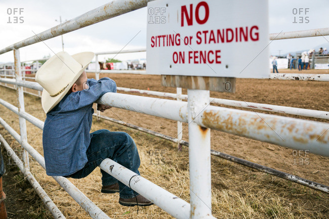 Taos, New Mexico, USA - June 28, 2015: Boy hanging on a rodeo fence