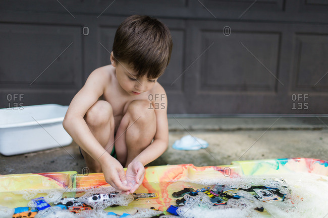 Boy plays with bubbles in soapy water filled with toy cars