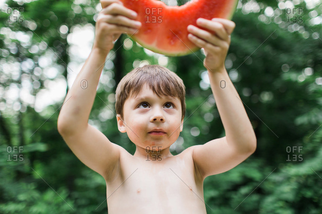 Boy with juice dripping from his chin holds up a slice of watermelon