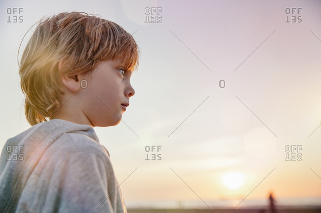 A boy on the beach at sunrise