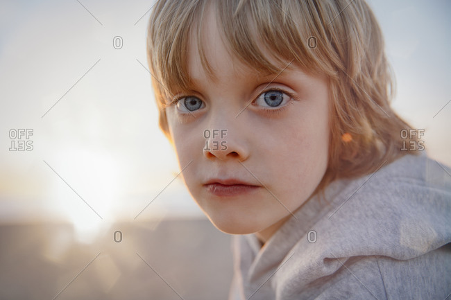 A portrait of a boy on the beach at sunrise