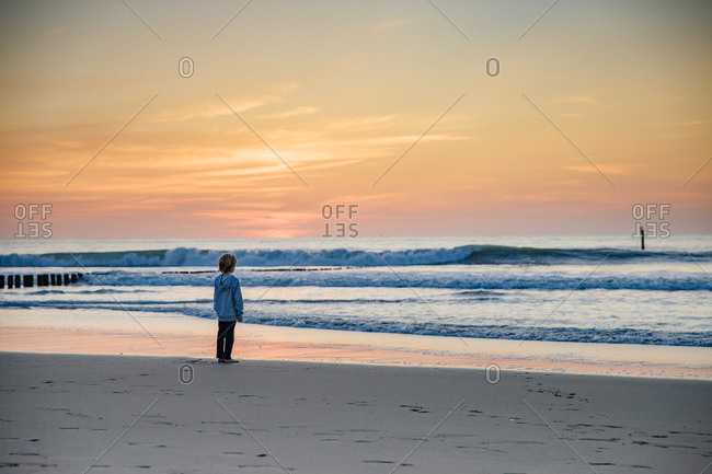 A boy looks at the ocean at sunset