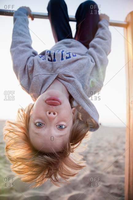 A boy hangs upside-down on the beach