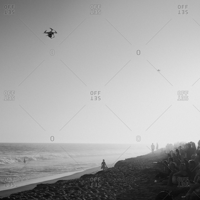 Drones in flight above a crowd sitting on beach at surf competition