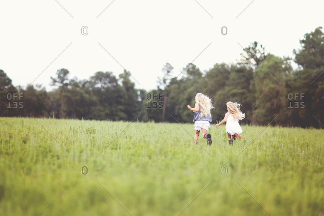 Two young blond girls run across a grassy meadow