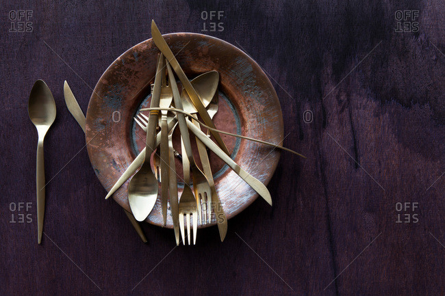Modern gold kitchen flatware piled on an old copper plate