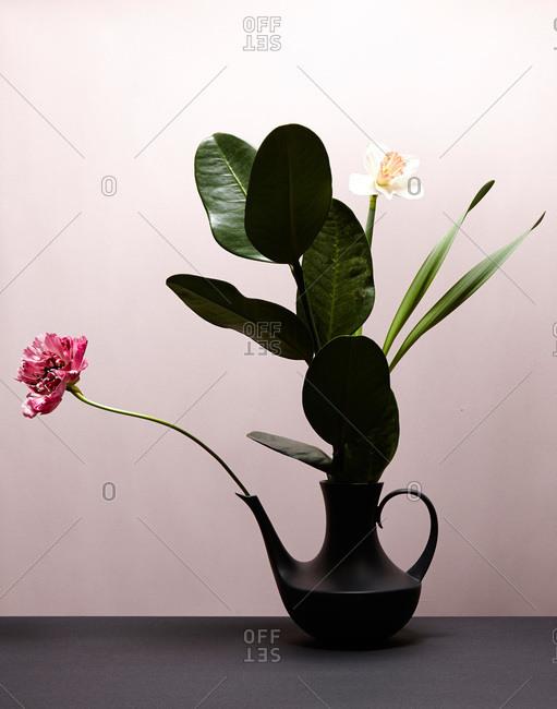 A flower arrangement in a black teapot