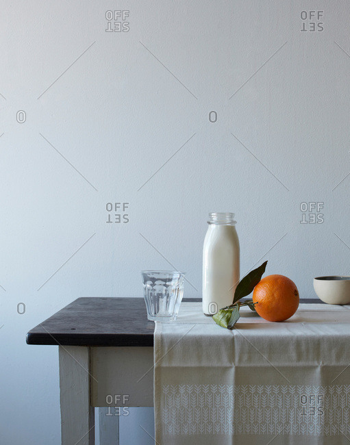 Milk and an orange on a simple table