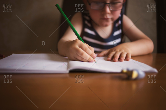 A boy writes in a notebook