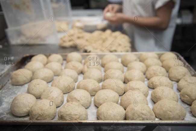 Baker forming fresh dough into bread rolls