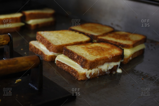 Many grilled cheese sandwiches on grill
