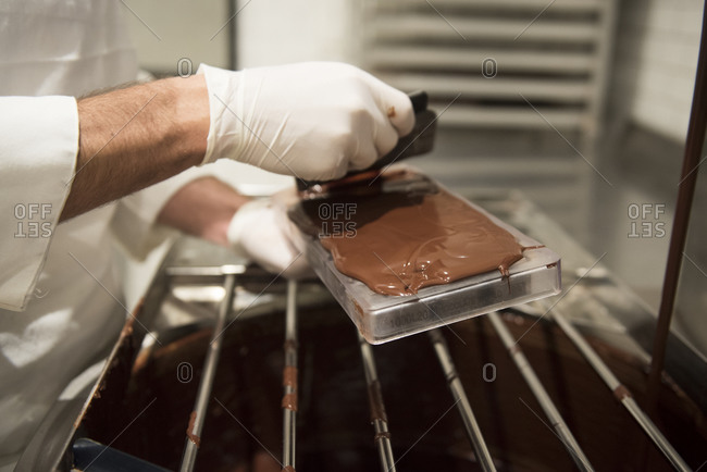 A person spreads warm  chocolate over a mold