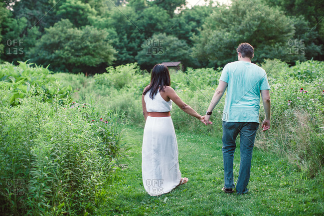 A couple holds hands in a field of grass