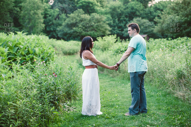 A couple holds hands in a field
