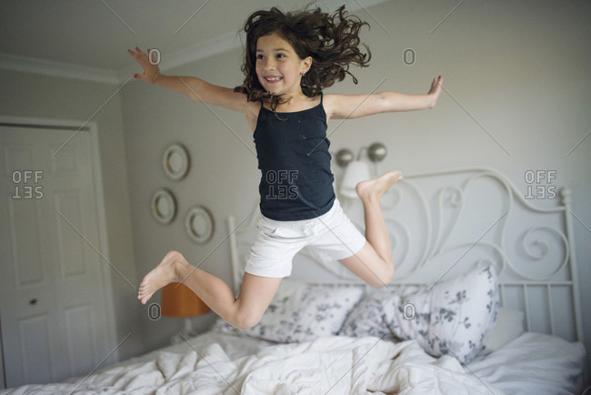 Little girl midair jumping on bed