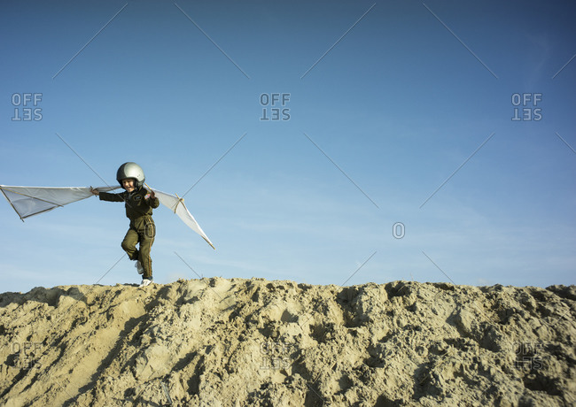 A Young Boy Dreaming Of Flying By Jumping The Dunes With Self Made Wings Stock Photo