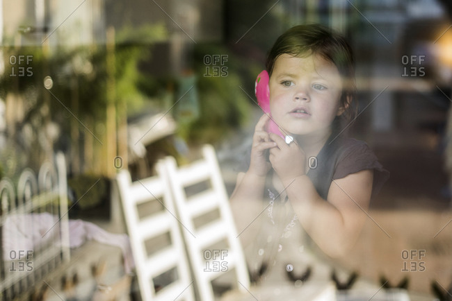 A girl pretending to make a phone call while looking out of the window