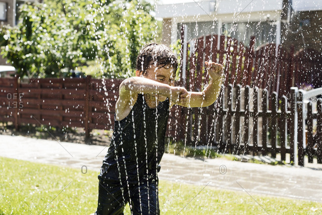 A boy running through a sprinkler a hot sunny day in summer