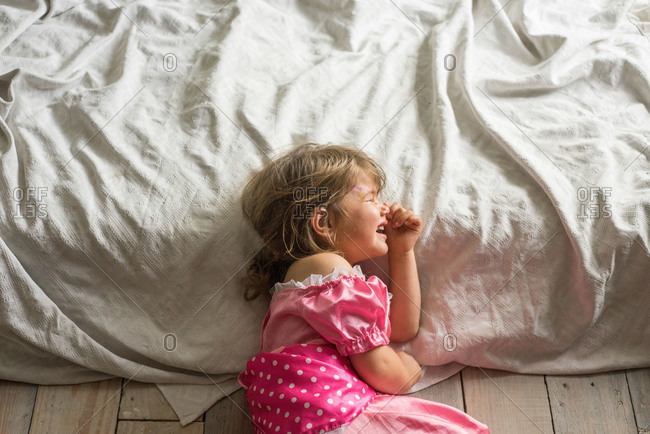 A little girl crying on the floor in a princess dress