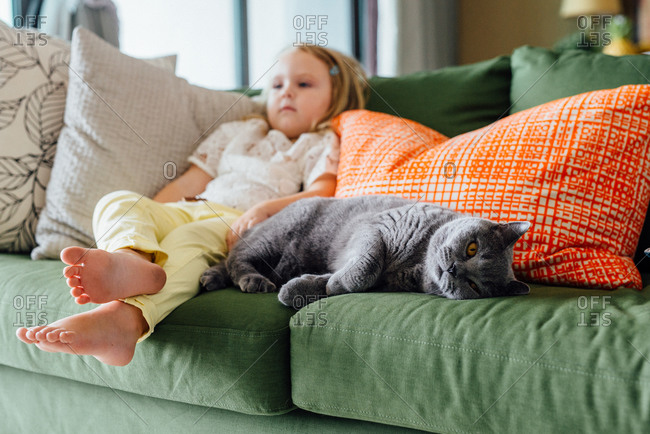 A girl and her cat rest on a couch