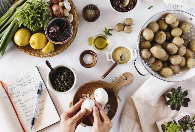 A woman peels eggs for a potato salad recipe
