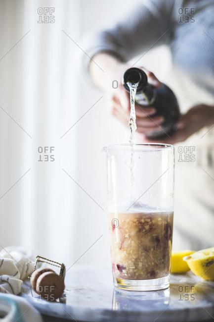 Pouring prosecco into a sangria pitcher