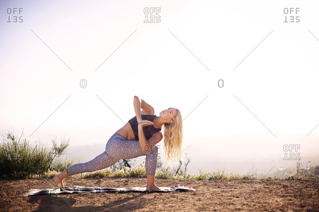 Woman in a twisted lunge with hands in prayer position outdoors