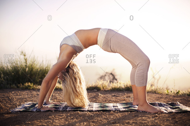 Woman in a backbend yoga pose outdoors
