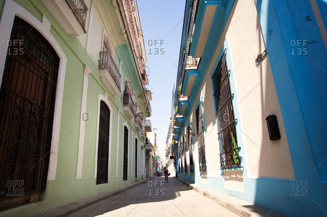 Woman walking down narrow alley with green and blue painted buildings on either side