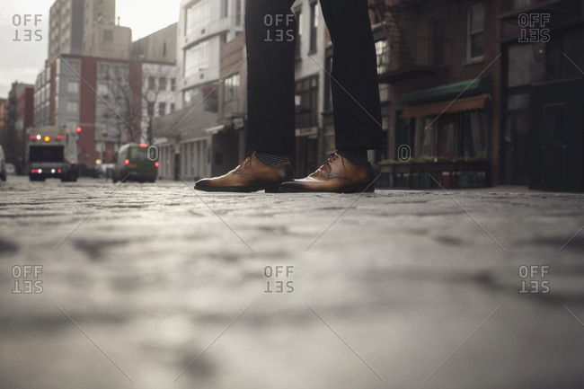 Stylish man's brown leather oxfords on cobblestone city street