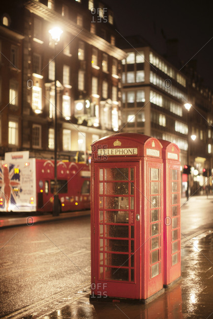 Two red telephone booths on a London street on a rainy evening