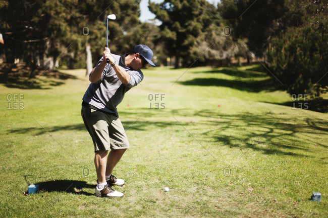 Golfer preparing to hit a ball on golf course