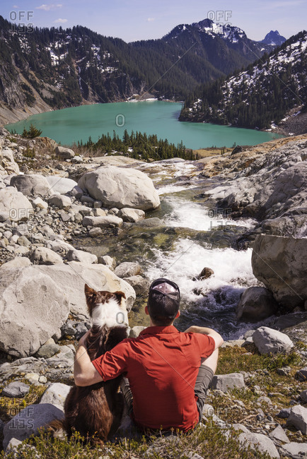 A man and his dog sit at the top of a mountain stream