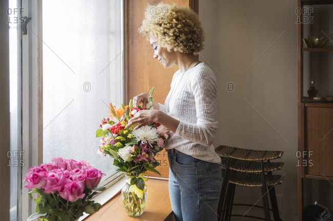A woman arranged a vase of flowers in her house