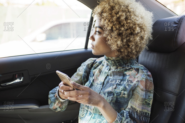 A young woman rides in the back of a taxi