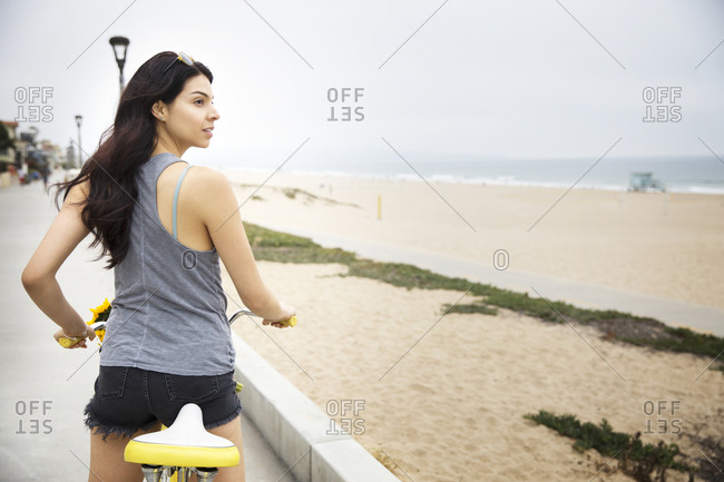 A woman on her bike looks towards the ocean