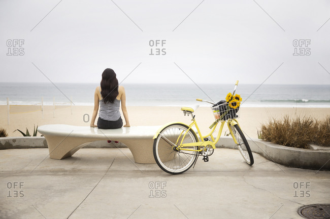 A woman sits by the beach with her bike