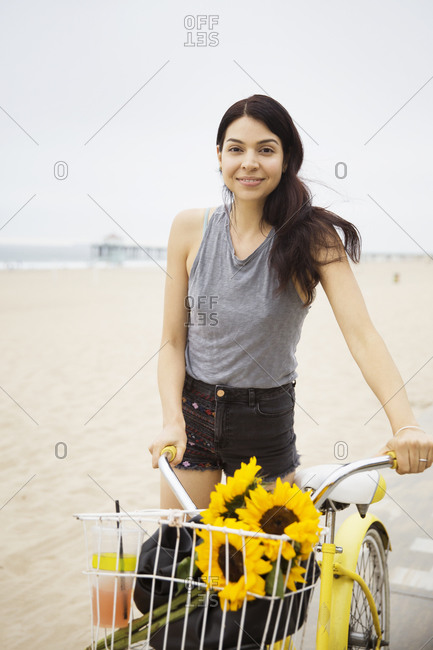A woman walks her bike on a path by the beach