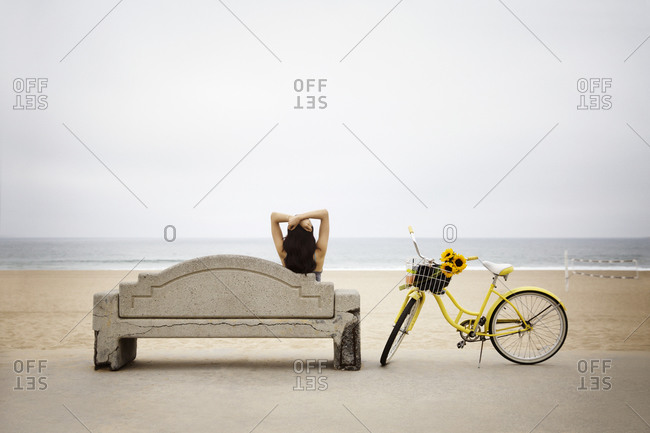 A woman sits on a bench by the beach
