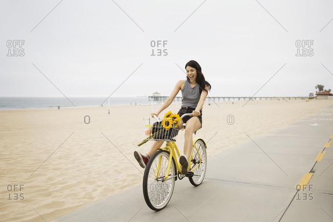 A woman rides her bike down a beach